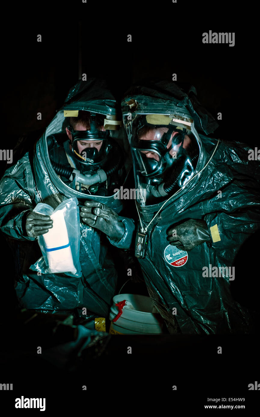 US Army national guard soldiers wearing HAZMAT Encapsulating Suits identify a potential radiological agent during - Stock Image