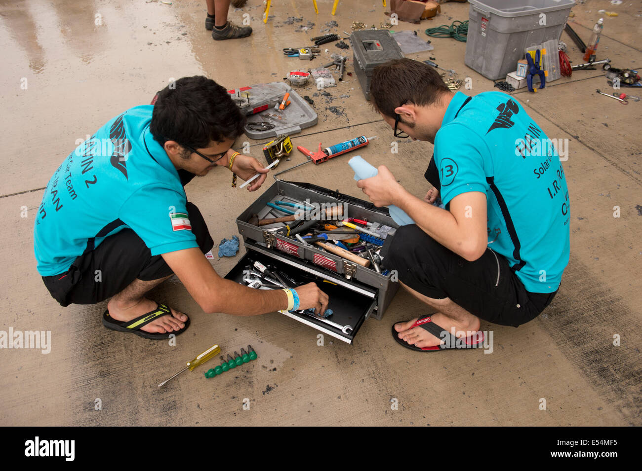 Iranian students help clean tools damaged in an overnight electrical fire in the garage area during qualifying races - Stock Image
