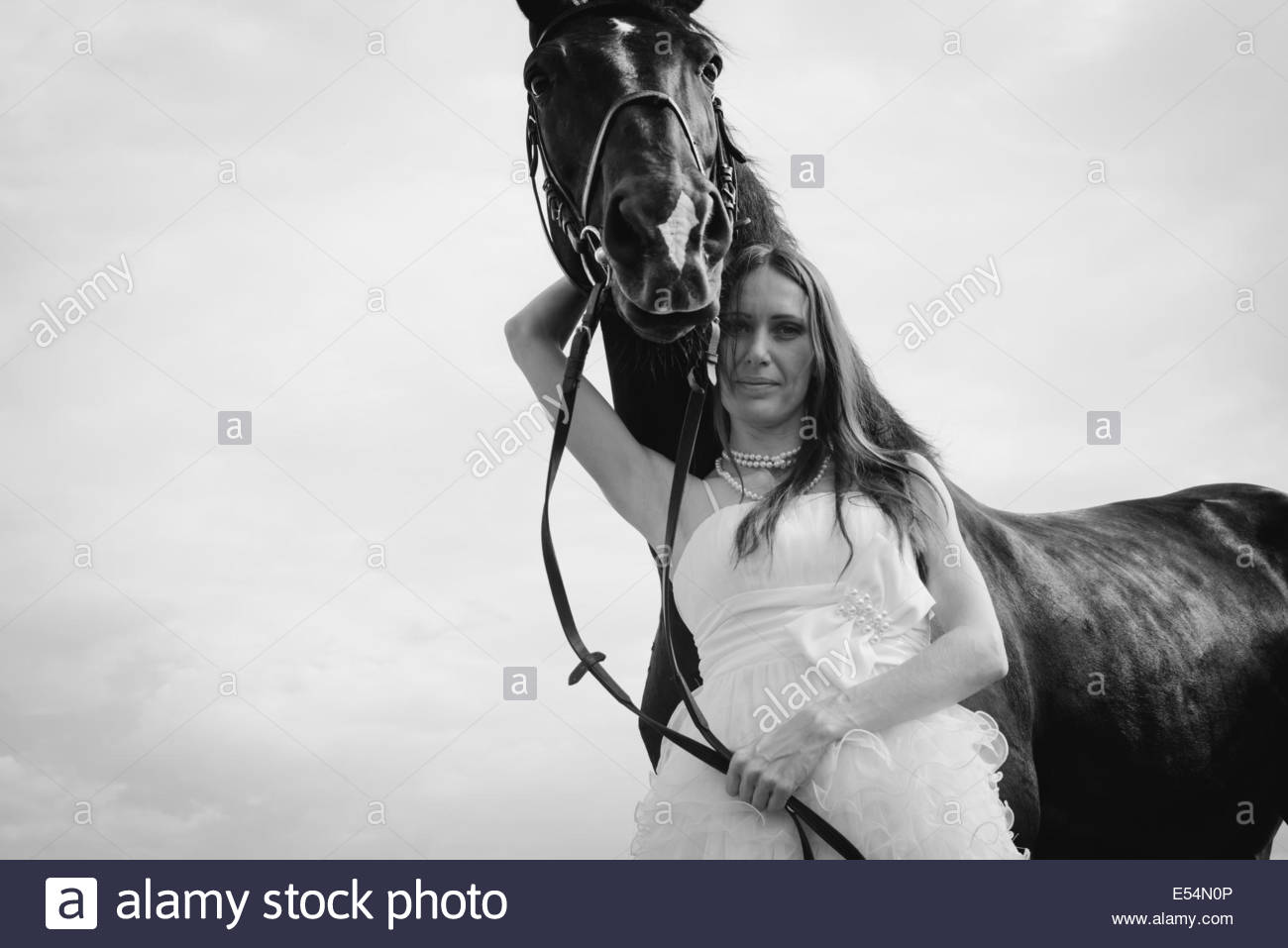 unusual bride at a wedding on black horse outdoors - Stock Image
