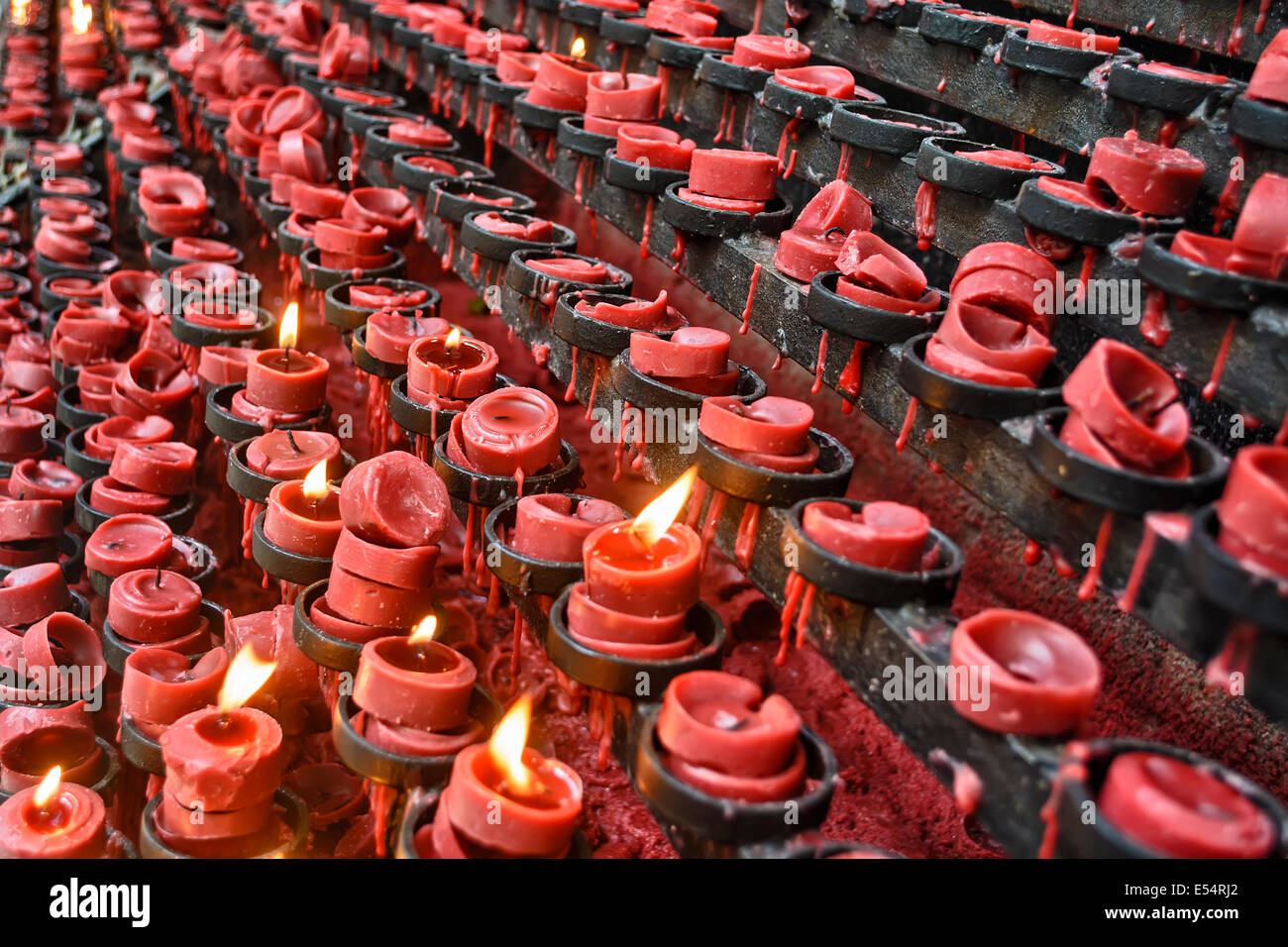 Lit and unlit red little candle offerings of people for their loved ones - Stock Image