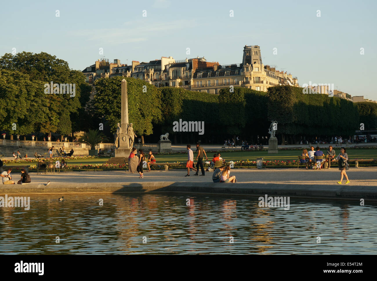 Summer shadows at Jardin du Luxembourg sunset, diverse tourists, Parisians relaxing in chairs reading, walking reflected - Stock Image