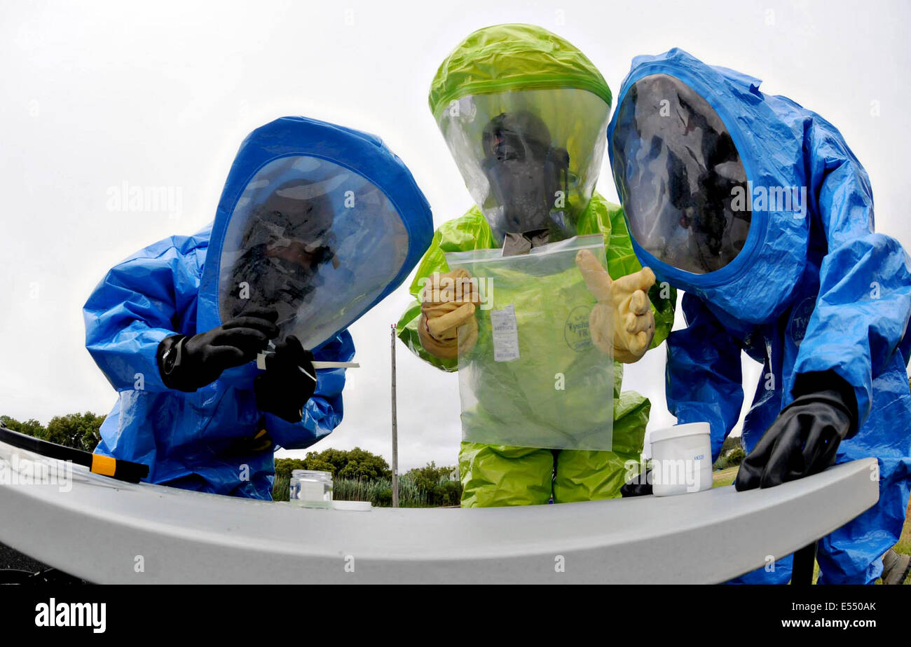Emergency management specialists wearing HAZMAT Encapsulating Suits tag and bag an unknown substance during a training - Stock Image