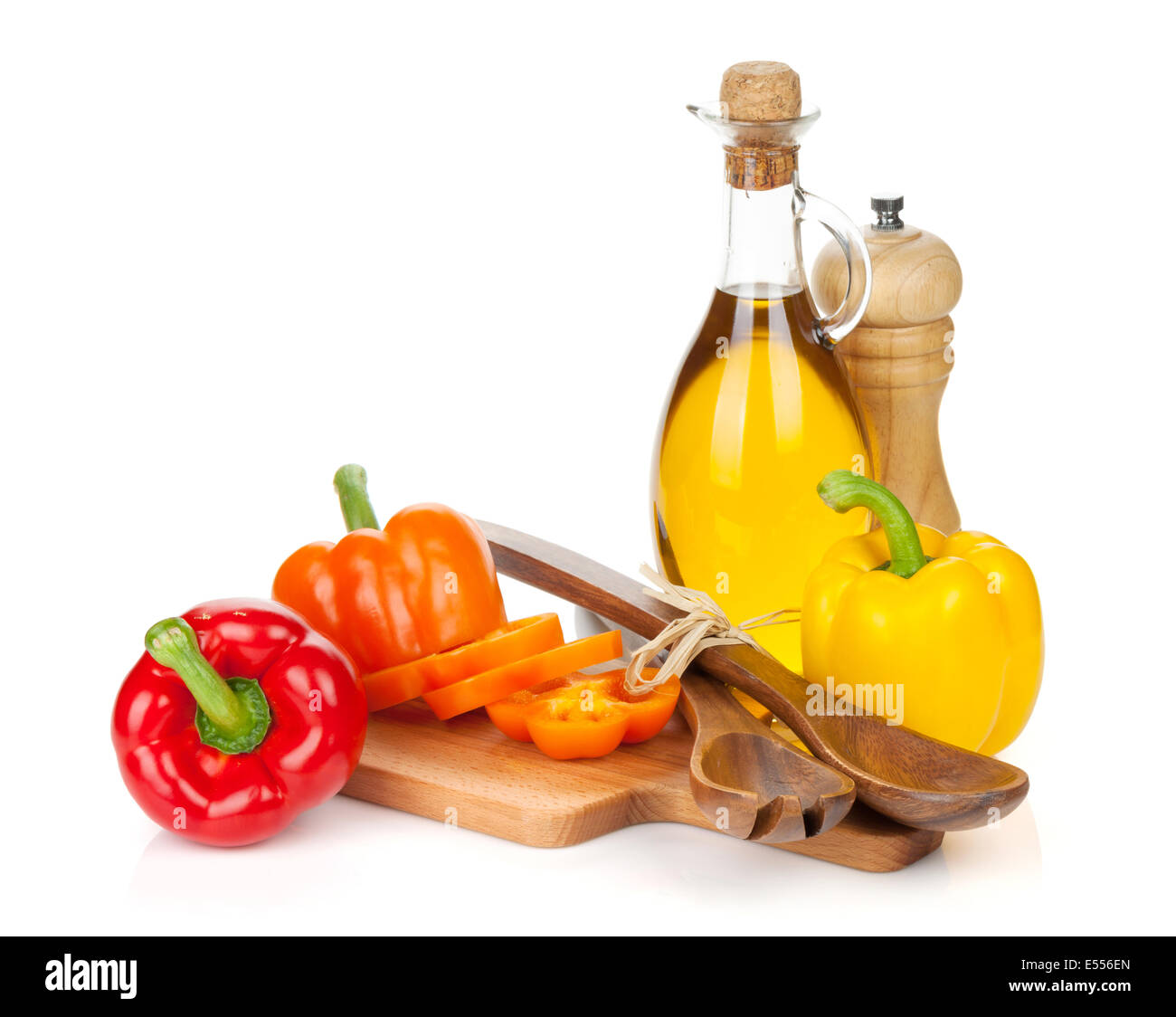 Colorful bell peppers and kitchen utensils. Isolated on white background - Stock Image
