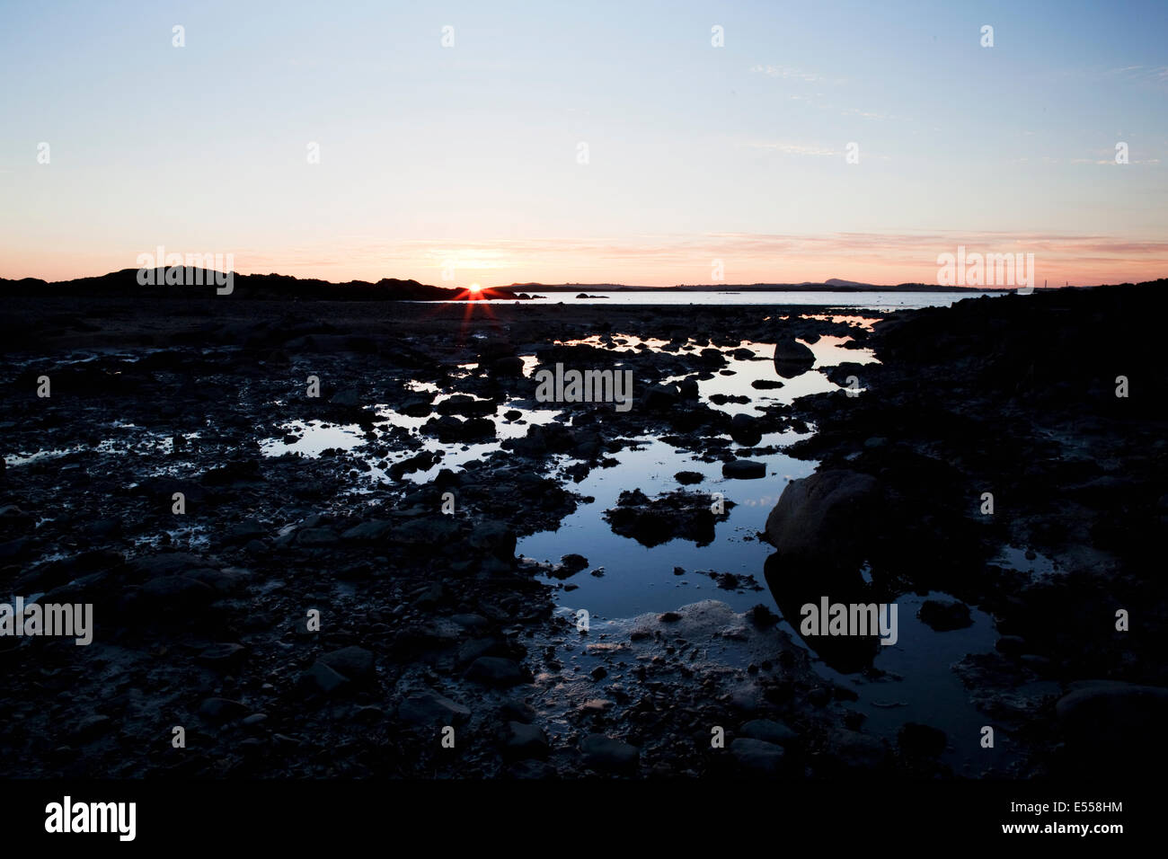 sun setting over rockpools, Boating Beach, Rhosneigr, Anglesey, North Wales - Stock Image