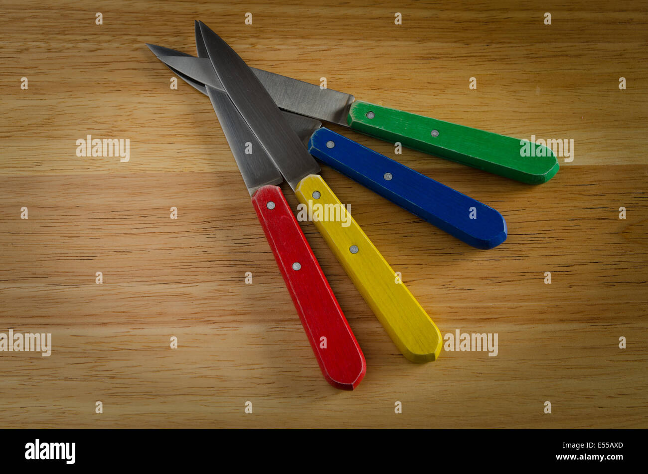 knifes on wood, red, yellow, blue, green - Stock Image
