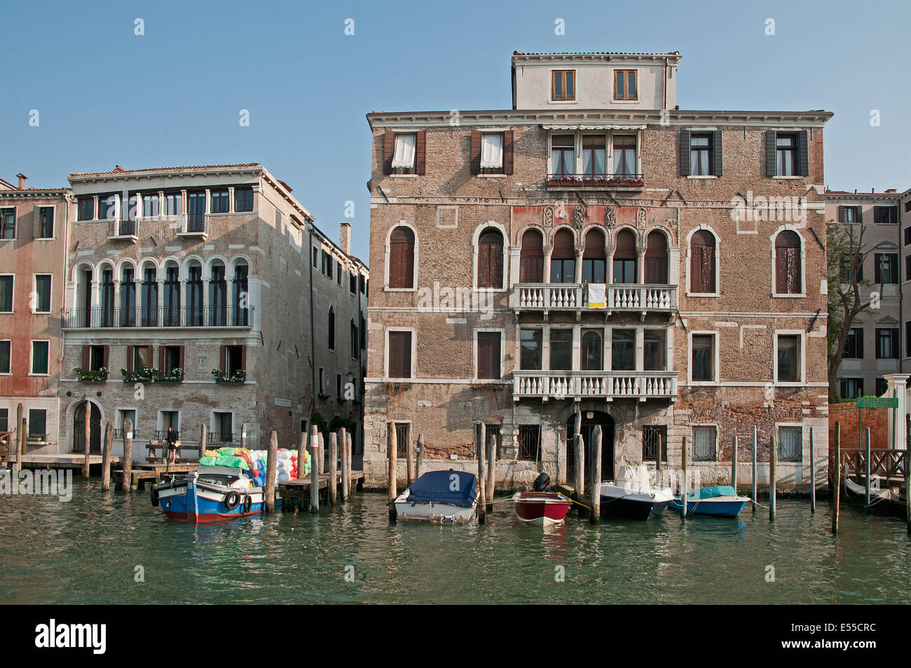 Substantial palace buildings houses palazzo pallazi with moored motor boats on the Grand Canal Venice Italy  GRAND - Stock Image