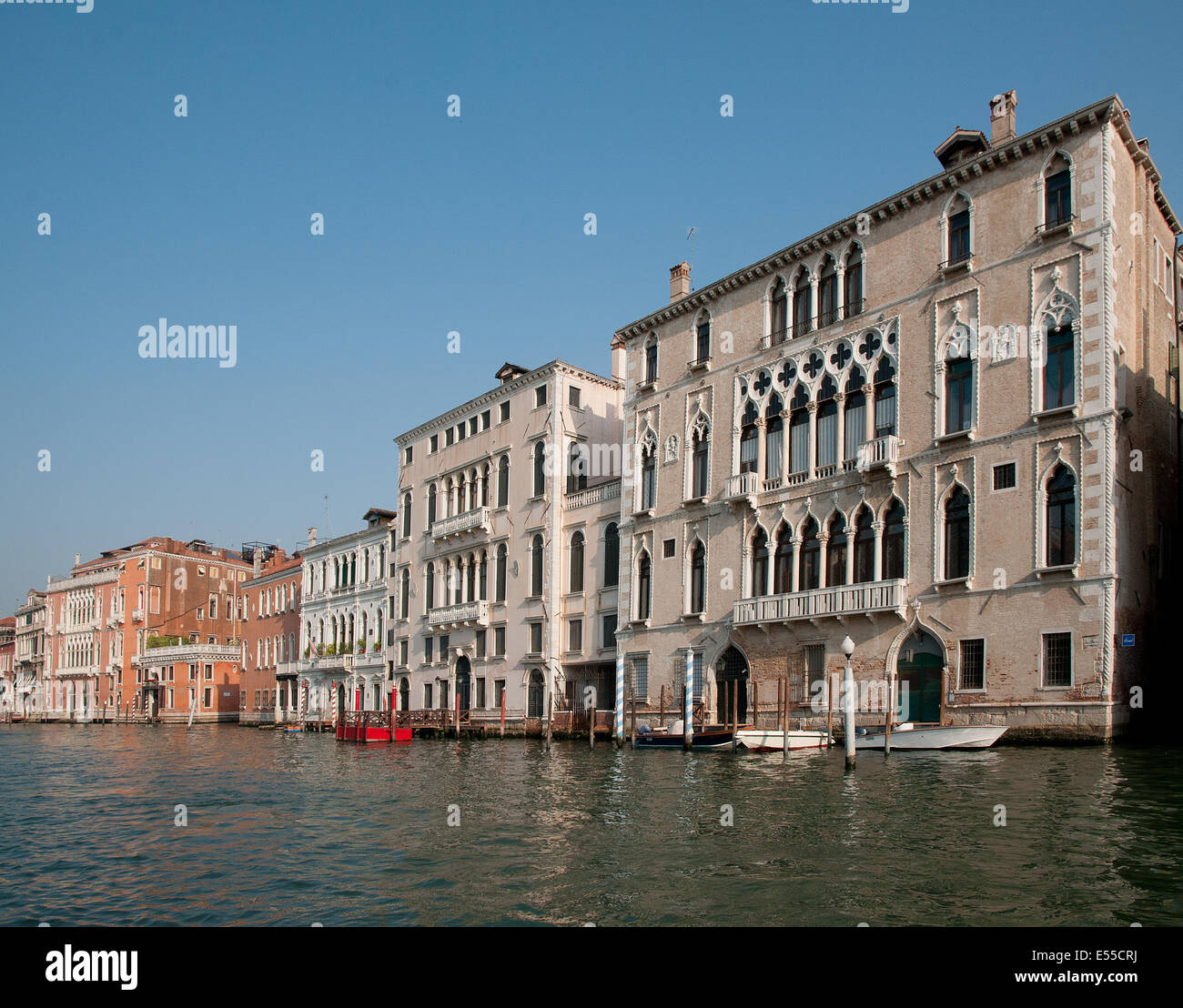 Beautiful palaces buildings houses palazzo pallazi with moored motor boats on the Grand Canal Venice Italy  GRAND - Stock Image