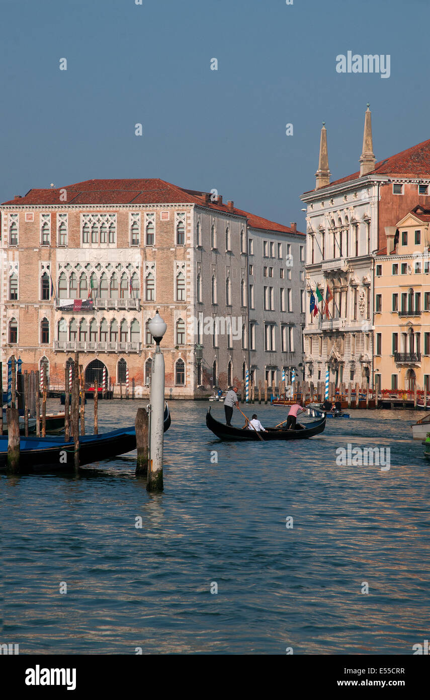 A gondola crossing the Grand Canal Venice Italy and many beautiful palaces in early morning sunshine  GRAND CANAL - Stock Image