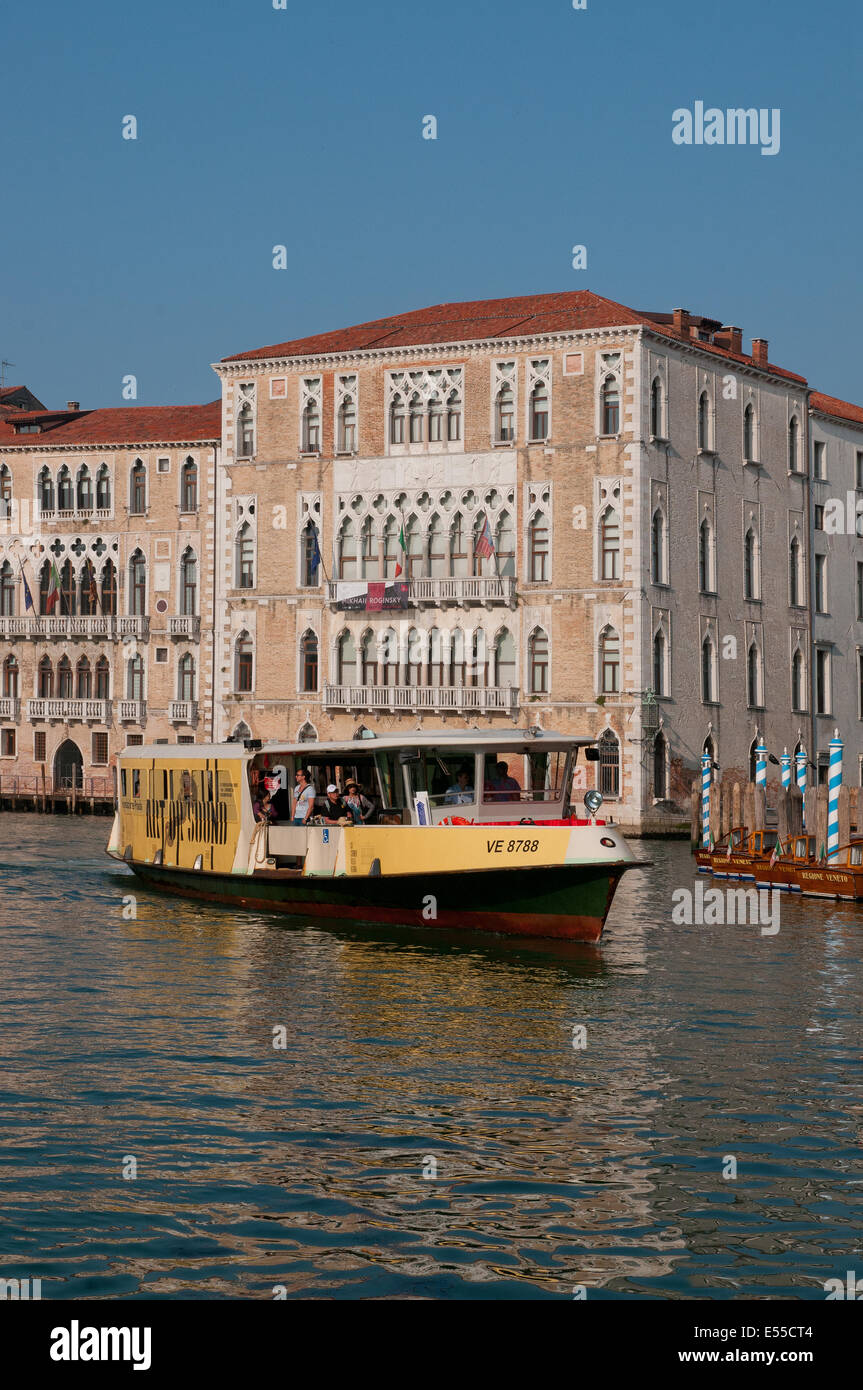 A Vaporetto water bus on the Grand Canal Venice Italy with beautiful palaces in early morning sunshine  GRAND CANAL - Stock Image