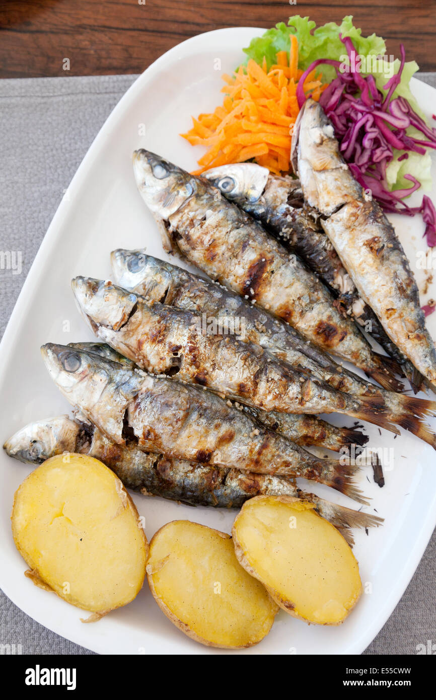 Plate of grilled sardines for a meal in a restaurant, Carvoeiro, Algarve Portugal, Europe - Stock Image
