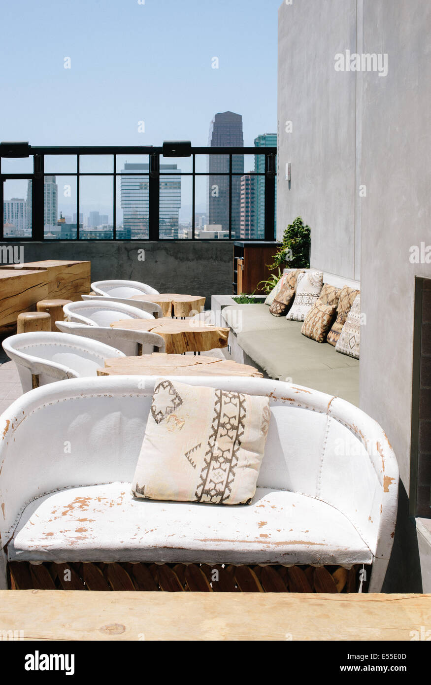 rooftop seating with distressed loveseats and los angeles skyline in