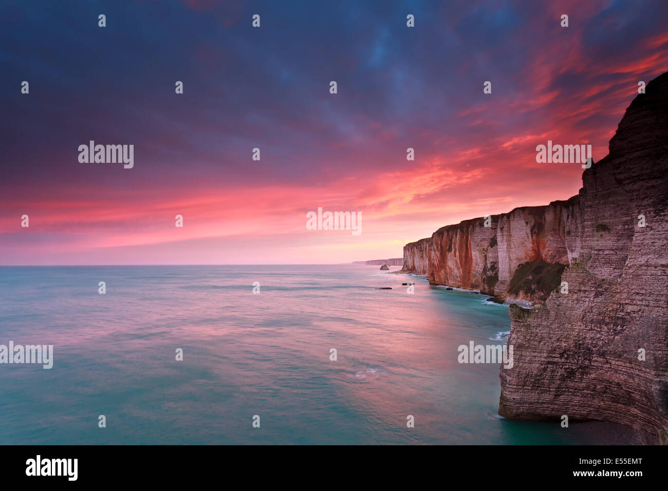 fire sunrise over cliffs in Atlantic ocean, France - Stock Image