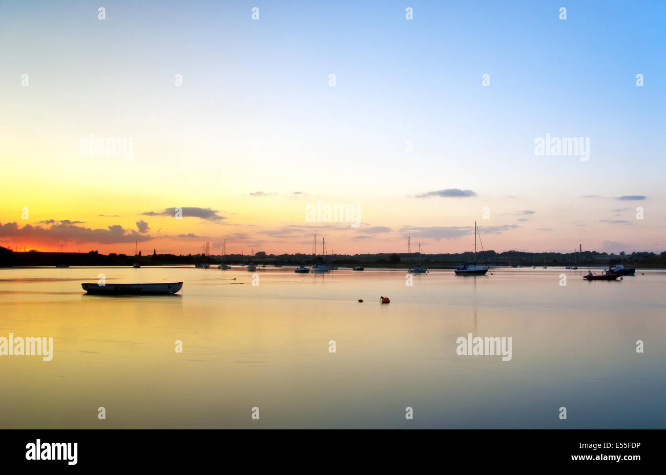An hour and half wait led to the sunset coinciding with the high tide. - Stock Image