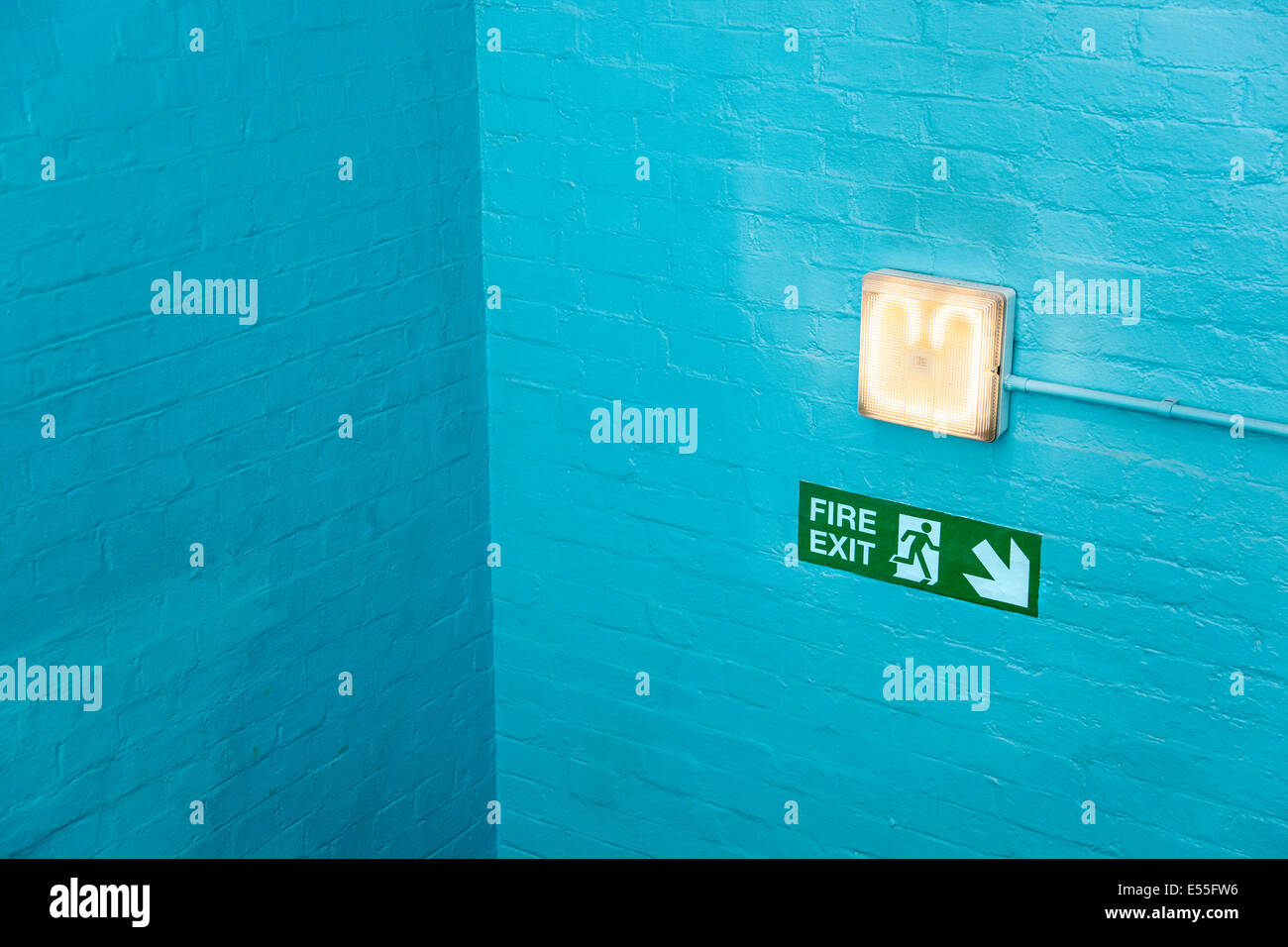 Blue wall corner with emergency exit sign and lamp - Stock Image