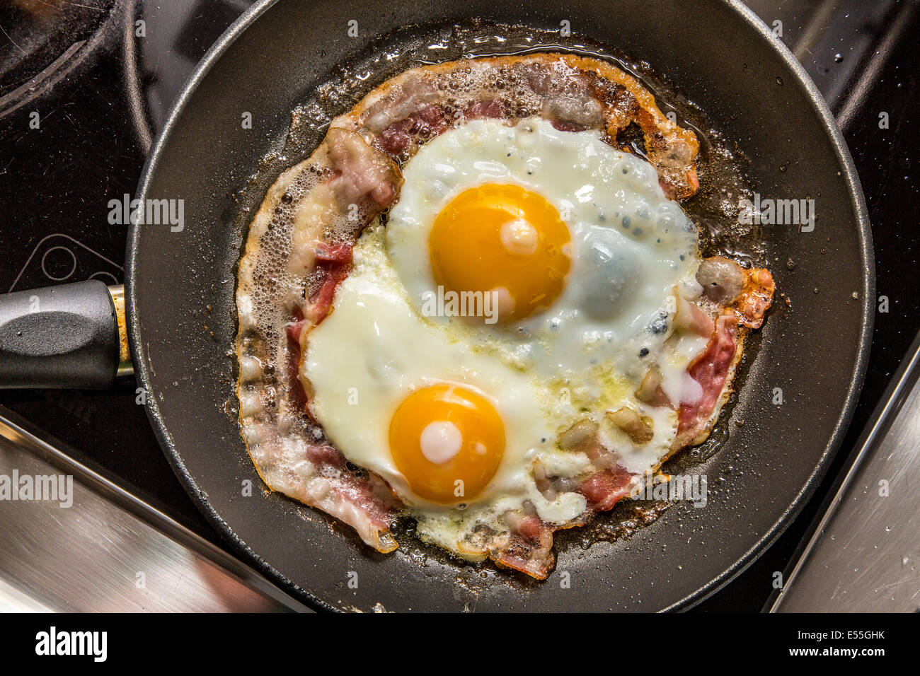 Fried eggs and bacon in a frying pan, breakfast, - Stock Image