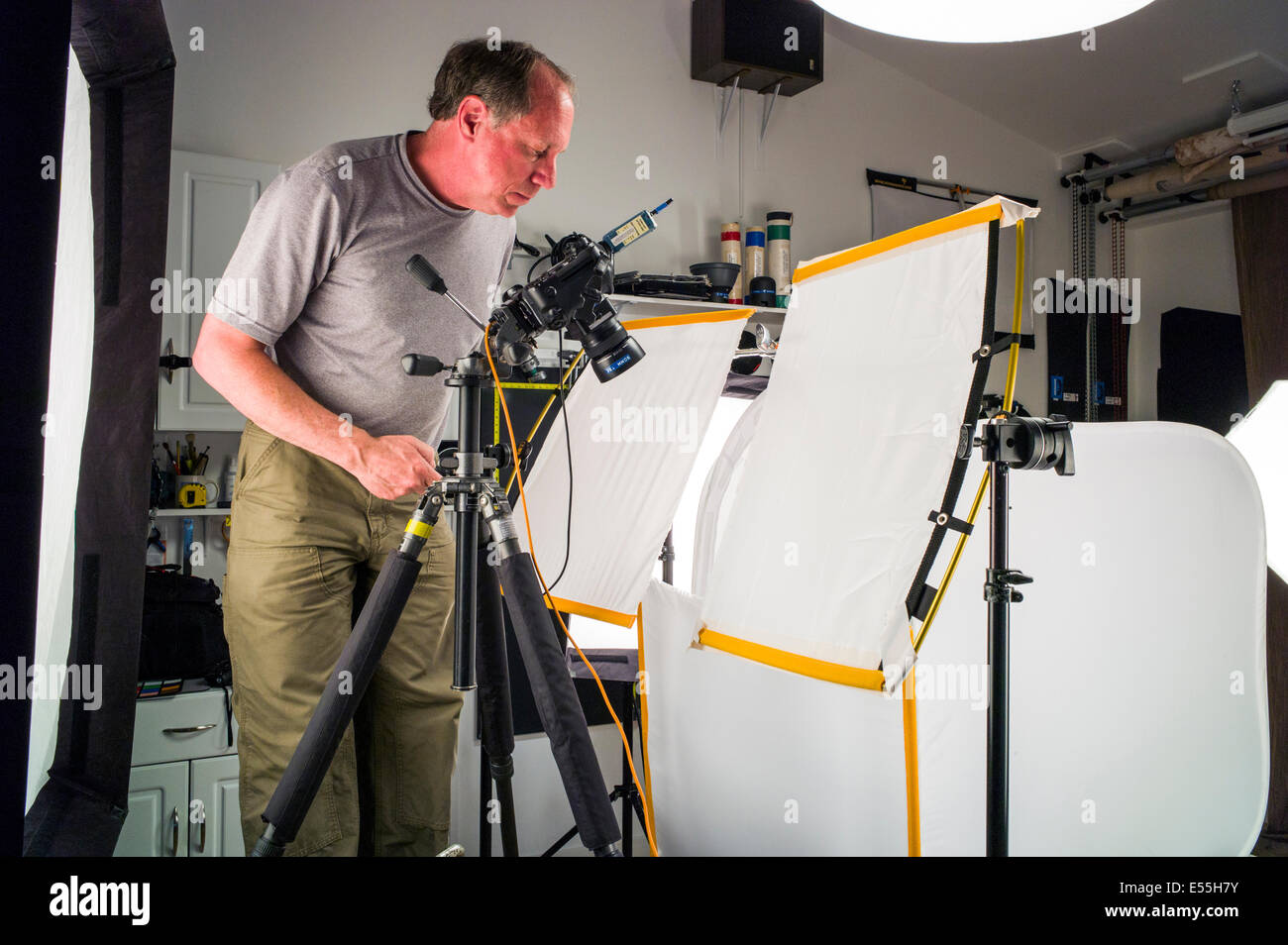 Photographer working on a commercial photography set, including lighting, background and grip gear. - Stock Image