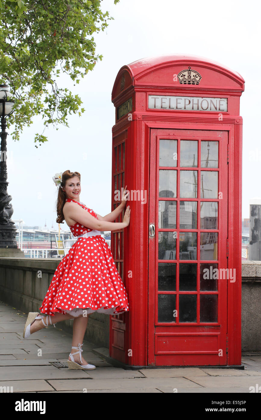Girl in red polka dot dress standing next to phone box - Stock Image