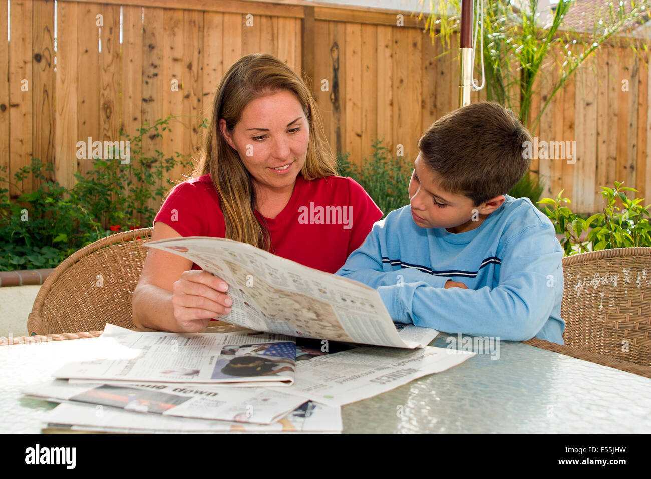 multi ethnic racial diversity racially diverse multicultural cultural mom child children son10-11 years old reading - Stock Image