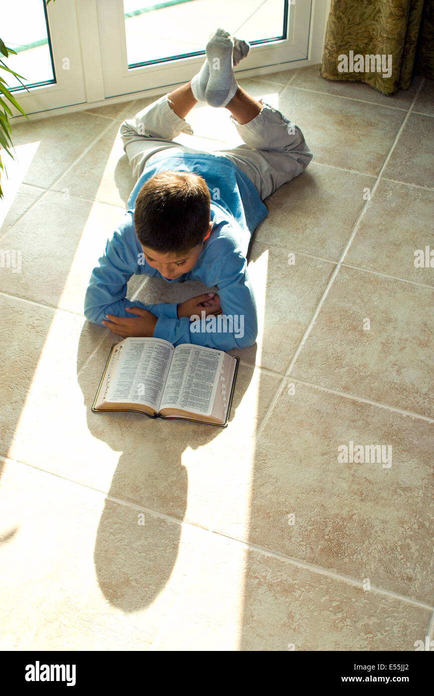 boy reading Bible multicultural multi-cultural Young Japanese/Caucasian 10-11 year years old children sunlight  - Stock Image