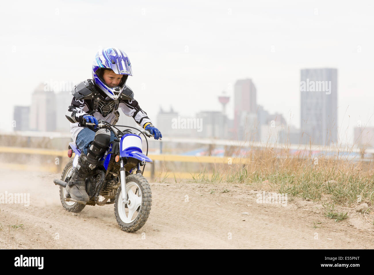 A young boy rides a motorcycle on a dirt track in front of the skyline in Calgary, Alberta, Canada. - Stock Image