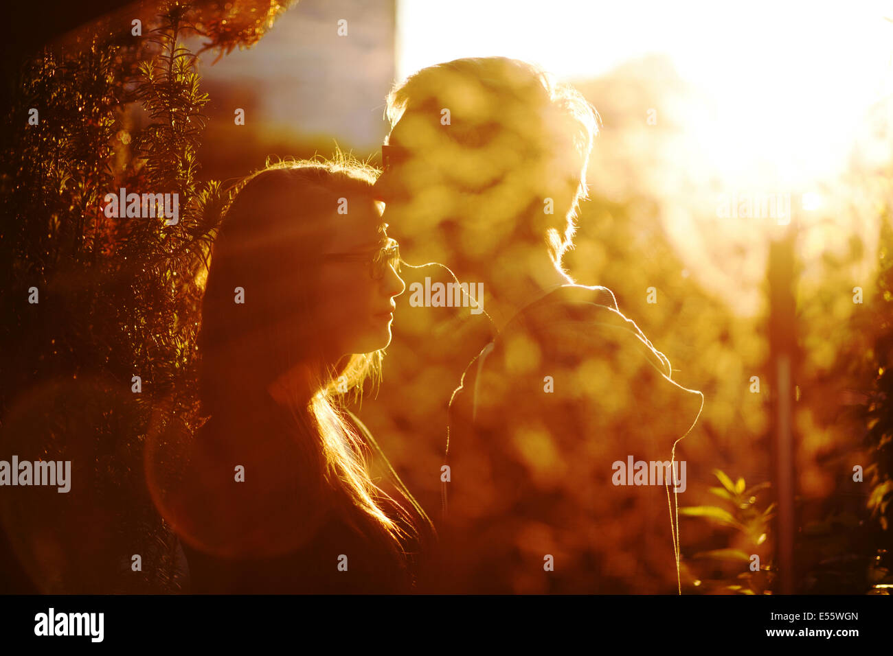 Young couple in love kissing in backlight - Stock Image