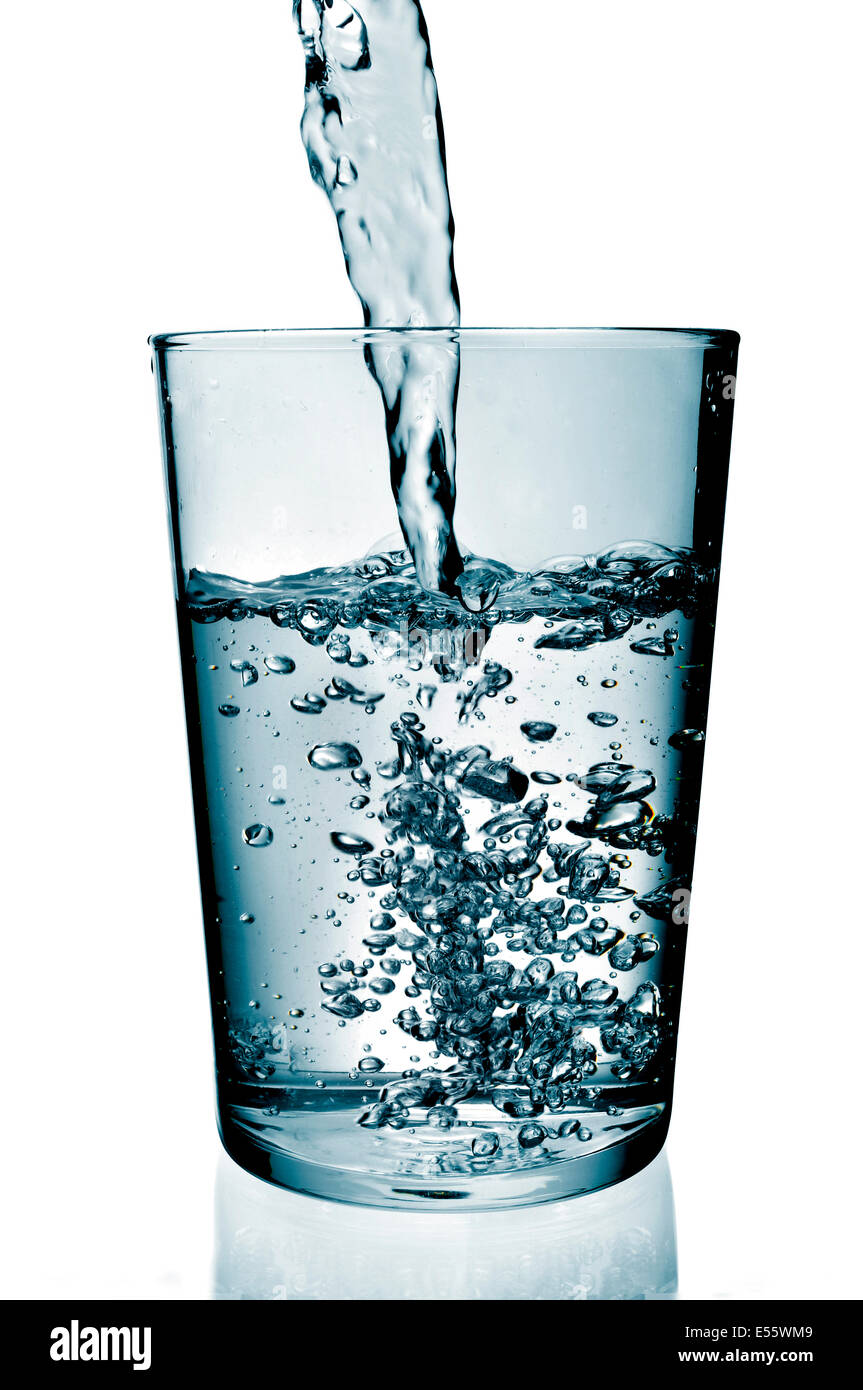a refreshing glass of water which is being filled - Stock Image