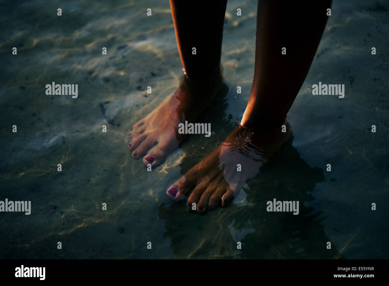 Woman standing barefoot in the water Stock Photo