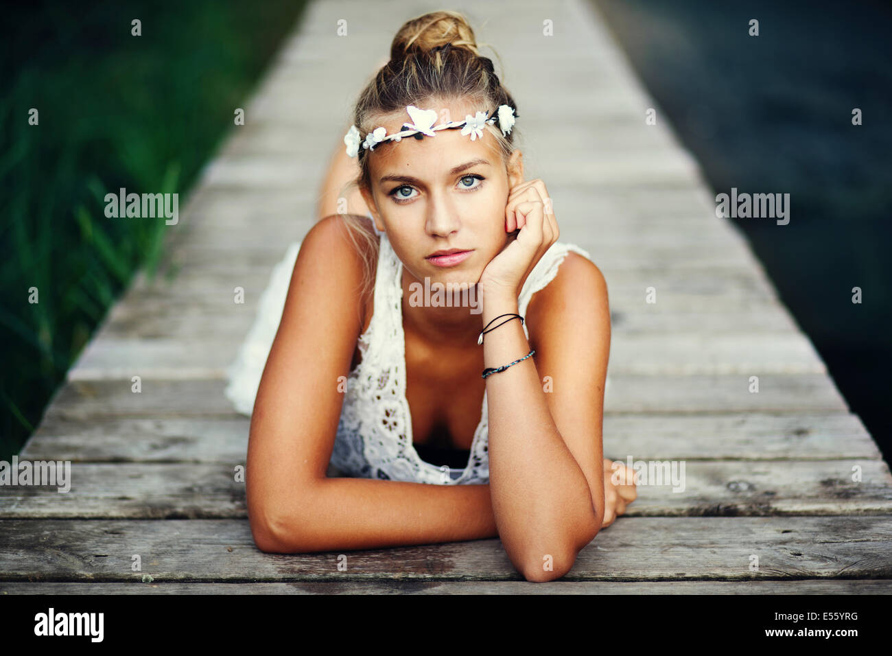 Young woman in white dress on a footbridge - Stock Image