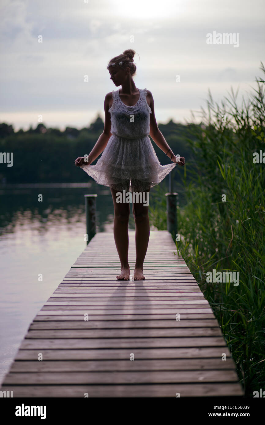 Young woman in white dress standing on a footbridge on the lake - Stock Image