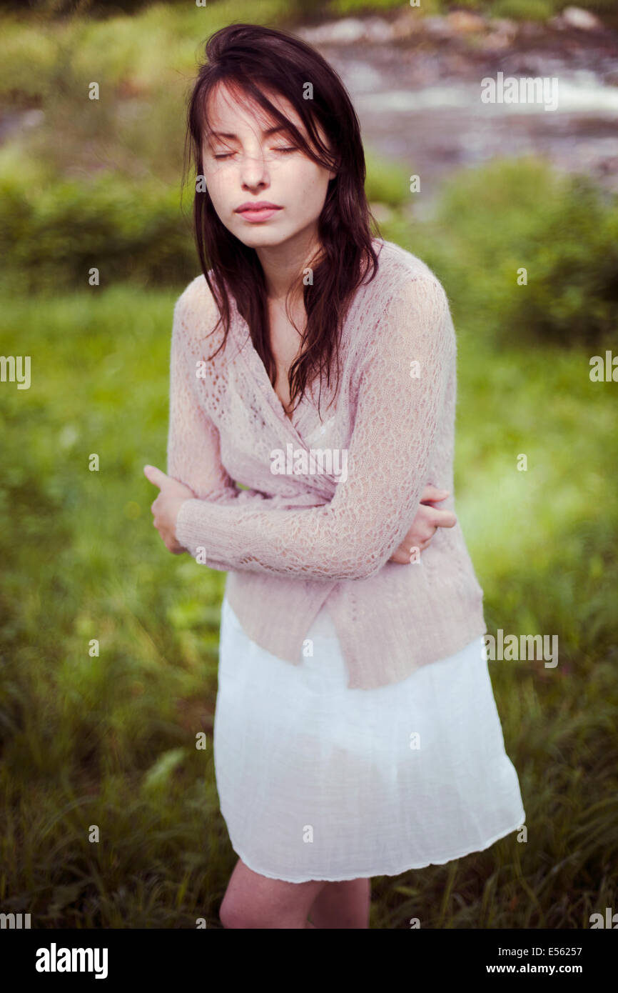 Young woman with arms crossed and eyes closed - Stock Image