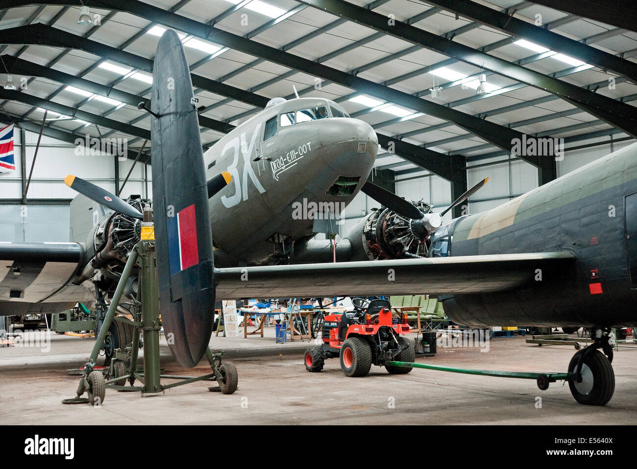 Framed by the tail of a Lancaster,  Dakota combat veteran Drag-Em-Oot undergoing maintenance in the hangar at Lincolnshire - Stock Image