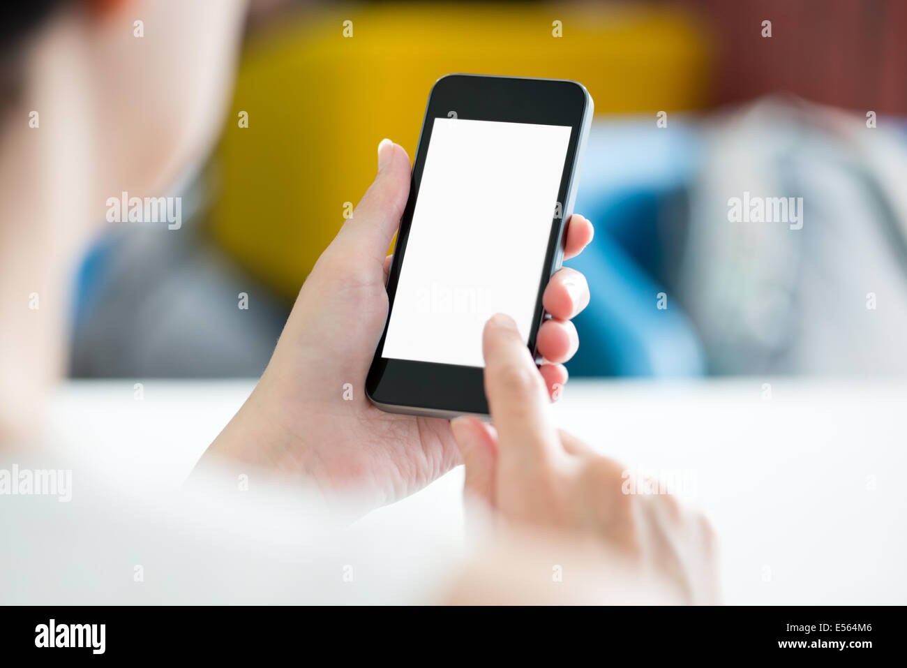 Woman with modern mobile phone in hands touching on a blank screen. Blurred office interior on a background. - Stock Image