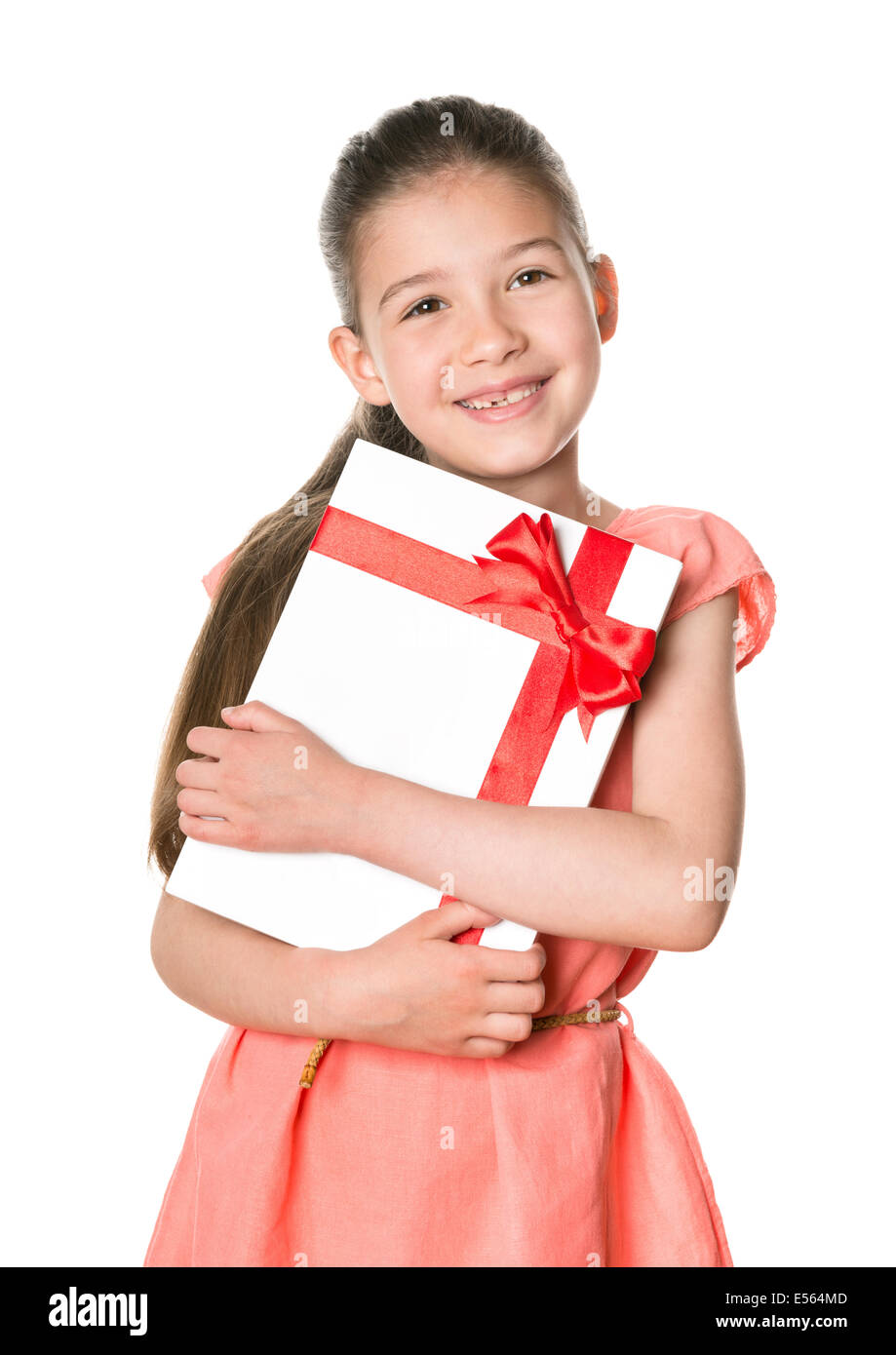 Smiling cute girl 8-9 years holding in hands birthday present in festive package. Isolated on a white background. - Stock Image