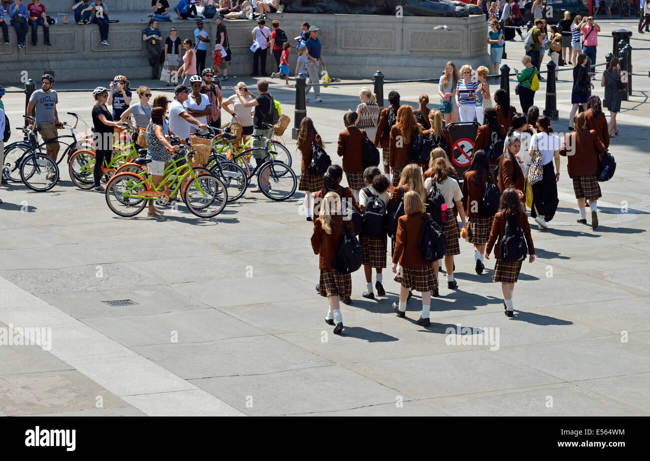 London, England, UK. Trafalgar Square: Schoolgirls in uniform on a school trip, and an organized cycling tour - Stock Image