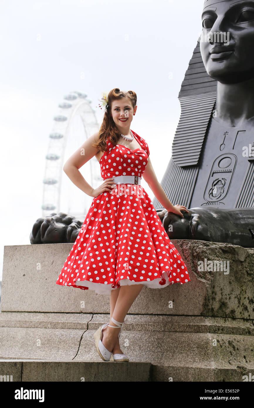 Girl in red polka dot dress beside the Sphinx on London Embankment - Stock Image