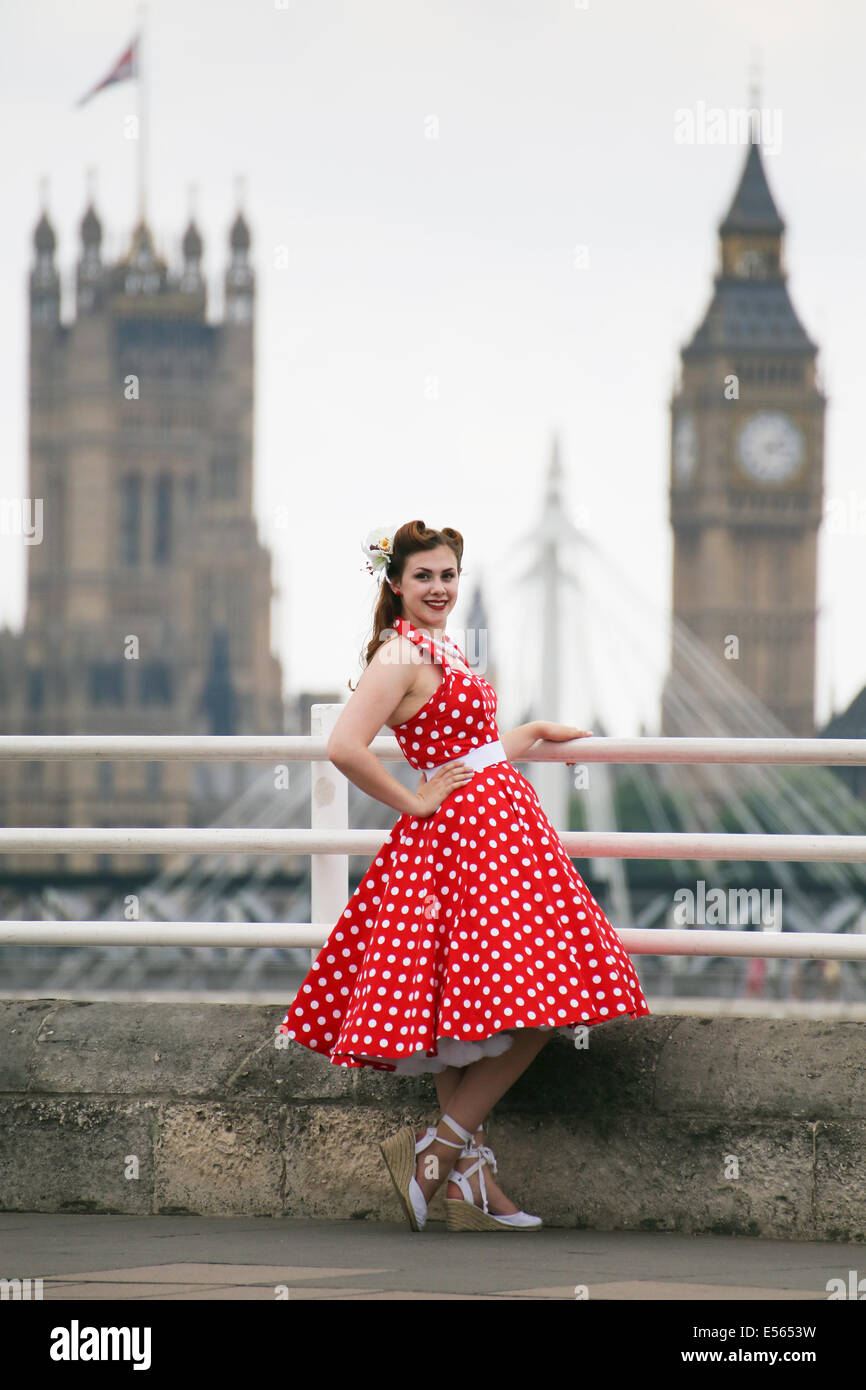 Woman in bright red polka dot dress on the embankment in front of Big Ben - Stock Image