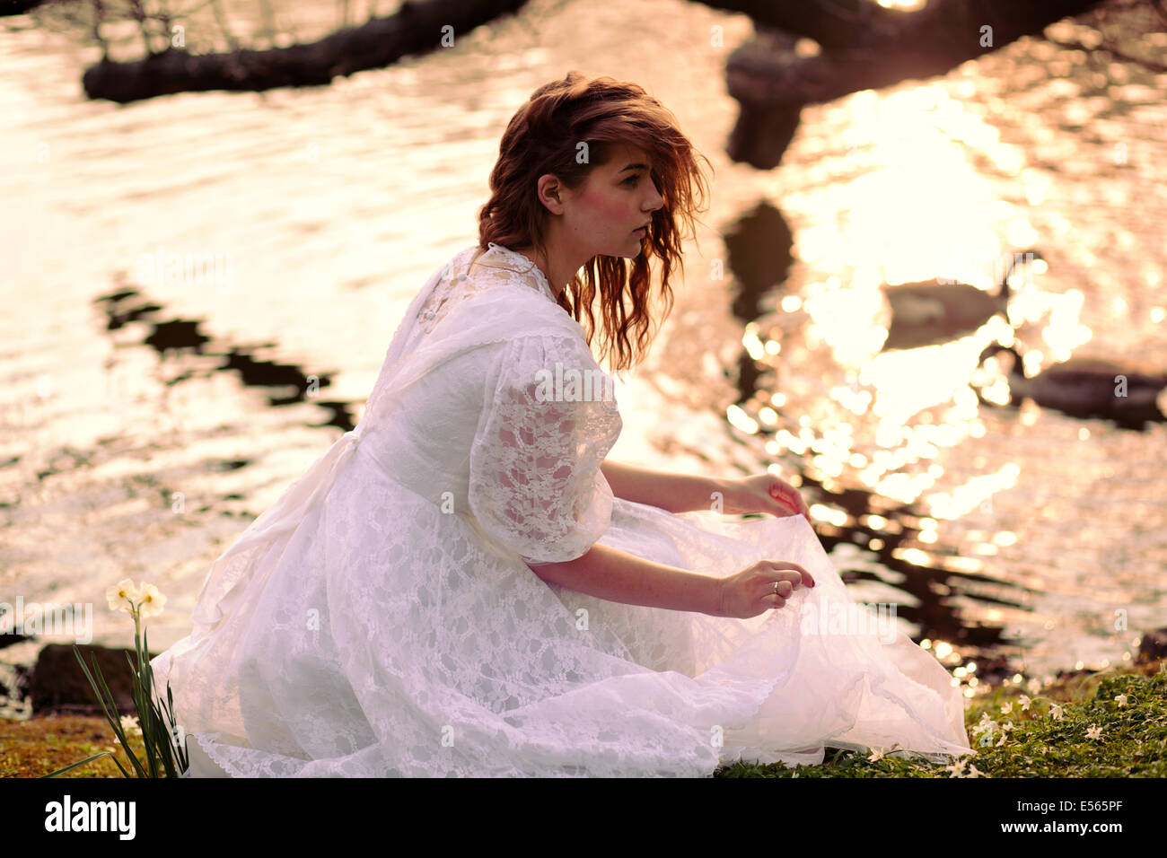 Young woman in white dress sitting by the lake - Stock Image