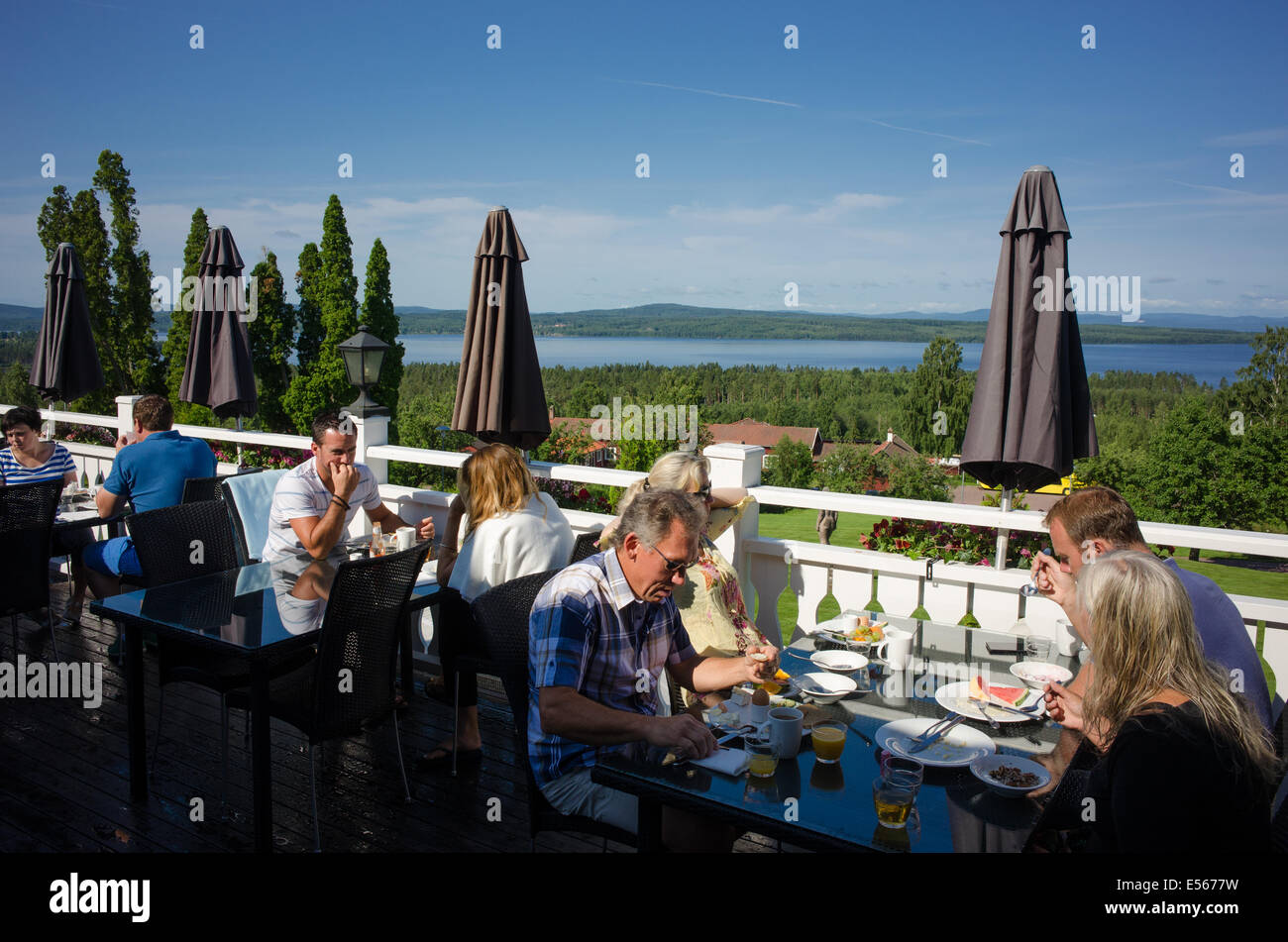 Tourists enjoy breakfast on a quiet summer morning at Lake Siljan in the Swedish folklore district Dalecarlia - Stock Image