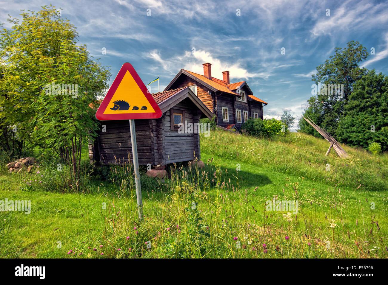 Traffic sign warning for hedgehogs crossing in idyllic Dalecarlia, Sweden Stock Photo