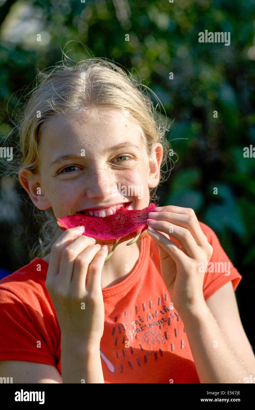 Young girl enjoys a Pitaya (AKA dragon fruit) - Stock Image