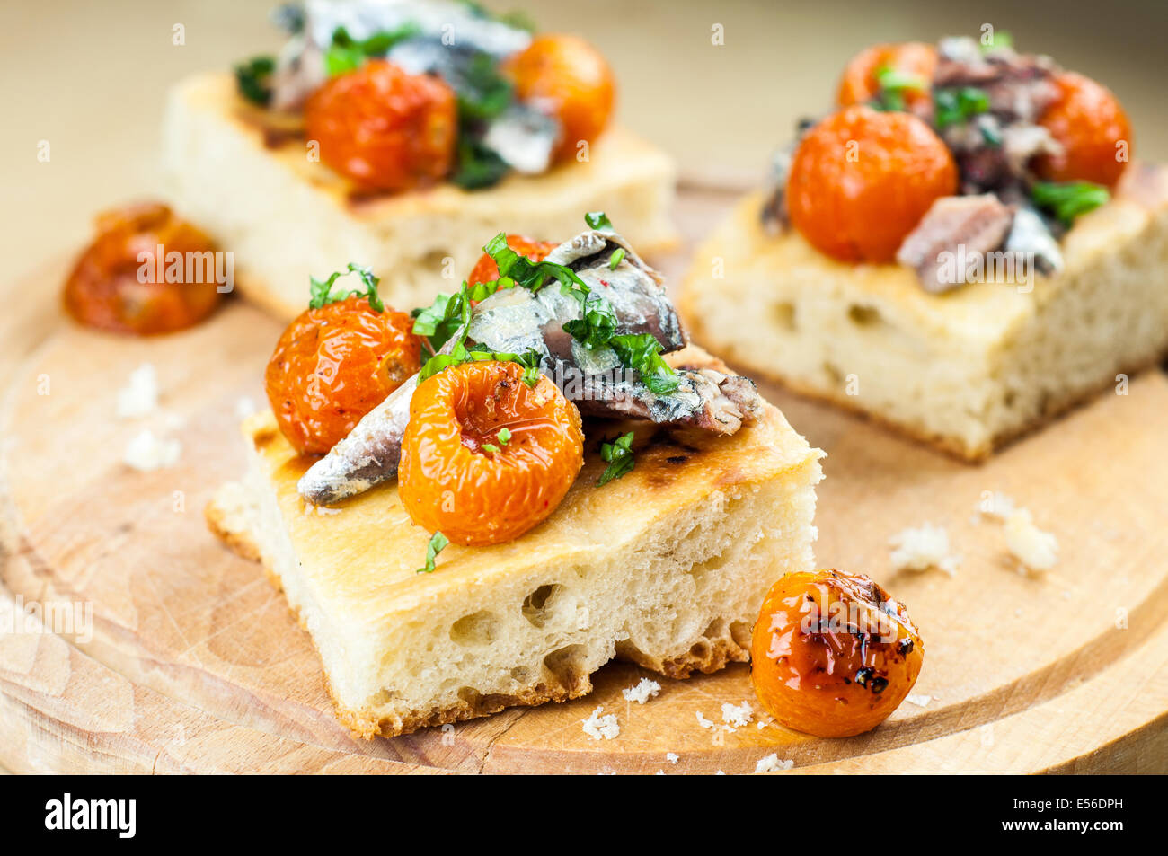 Delicious focaccia with sardines and cherry tomatoes on wood - Stock Image