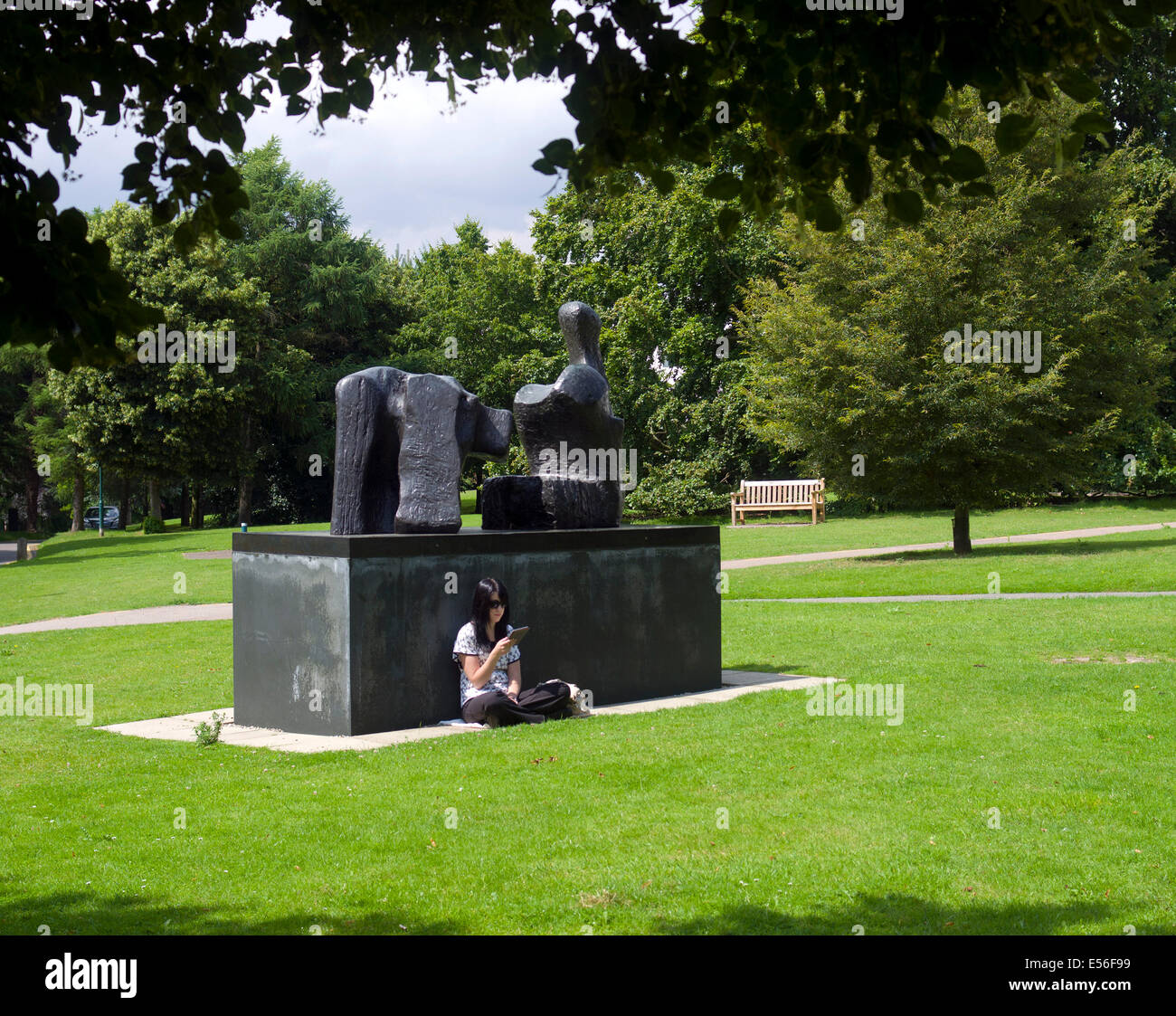 Bronze sculpture 1961 by Henry Moore sited by The Sainsbury Centre Norwich. Student reading leaning on the plynth - Stock Image