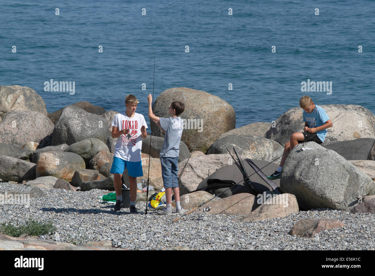 Teenage boys enjoying their summer holidays angling in the Sound, Øresund, from the Kronborg point at Helsingør - Stock Image