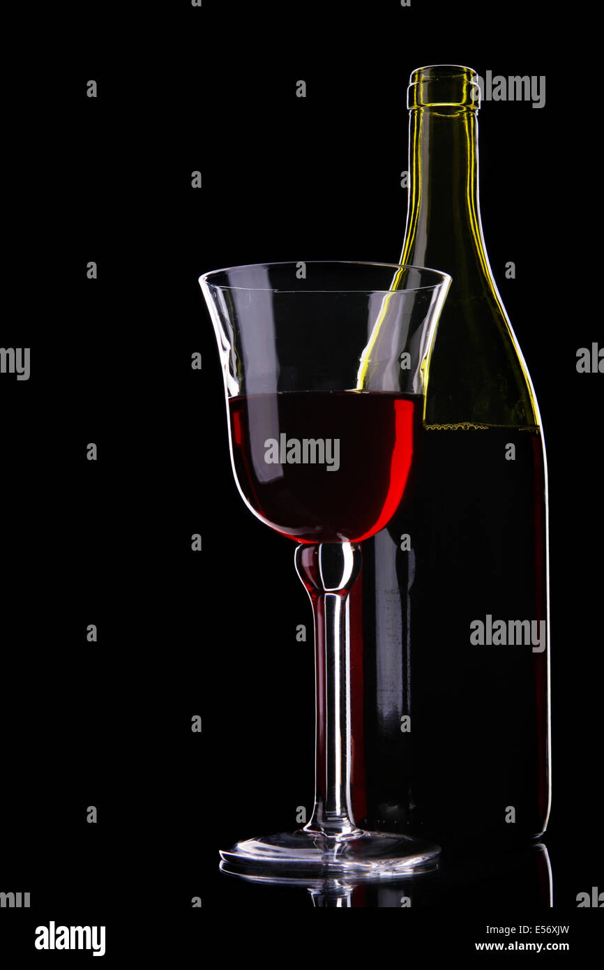 b40ea8c4e308 Still-life with bottle and glass of red wine over black background - Stock  Image