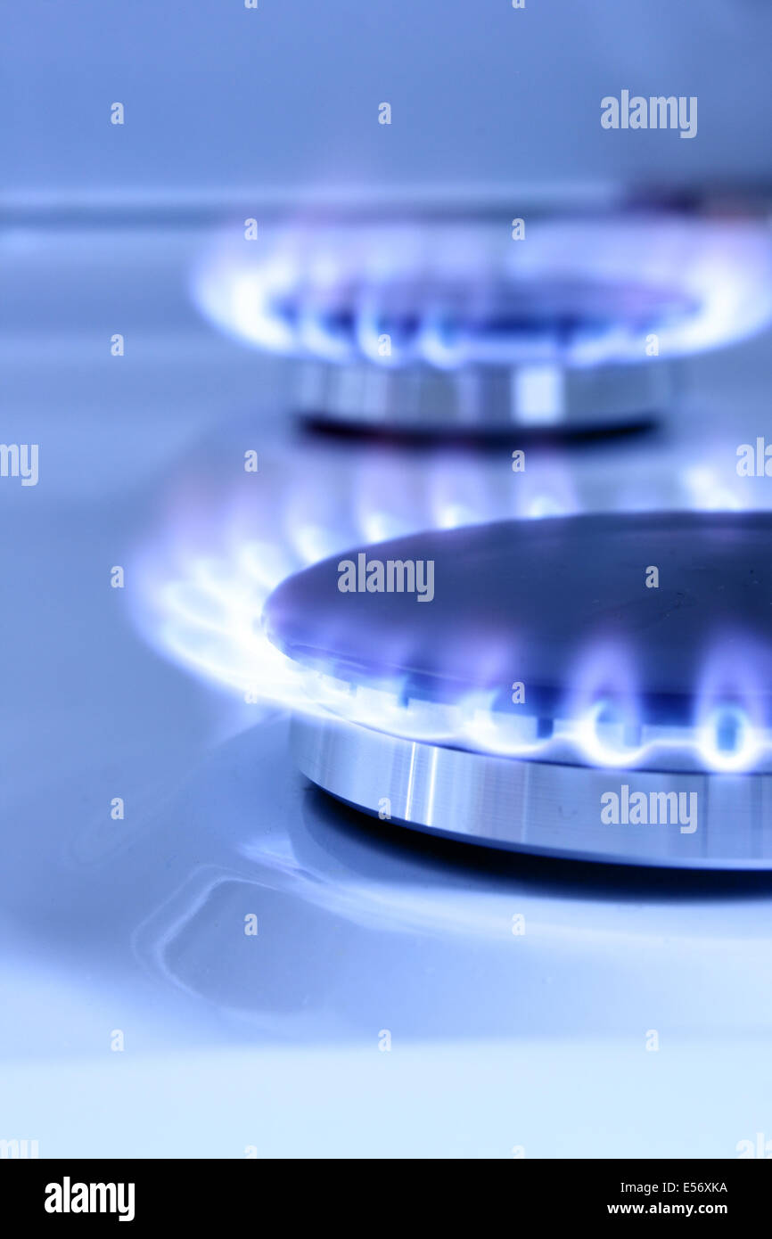 Blue gas flame on hob and space for text on left - Stock Image