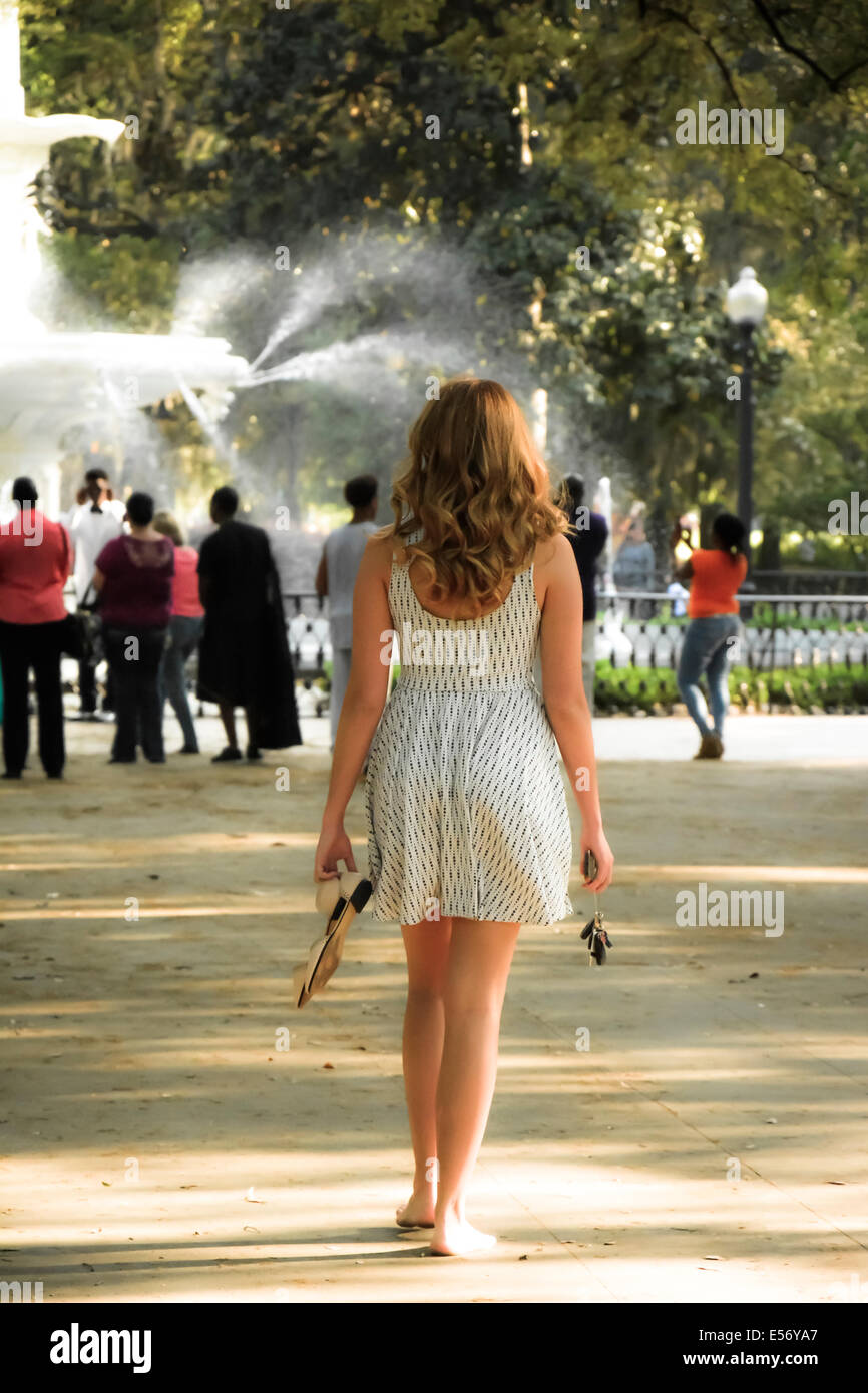 Rear view of a young white female with long hair walking barefoot in a sundress towards the Forsyth Park fountain, - Stock Image