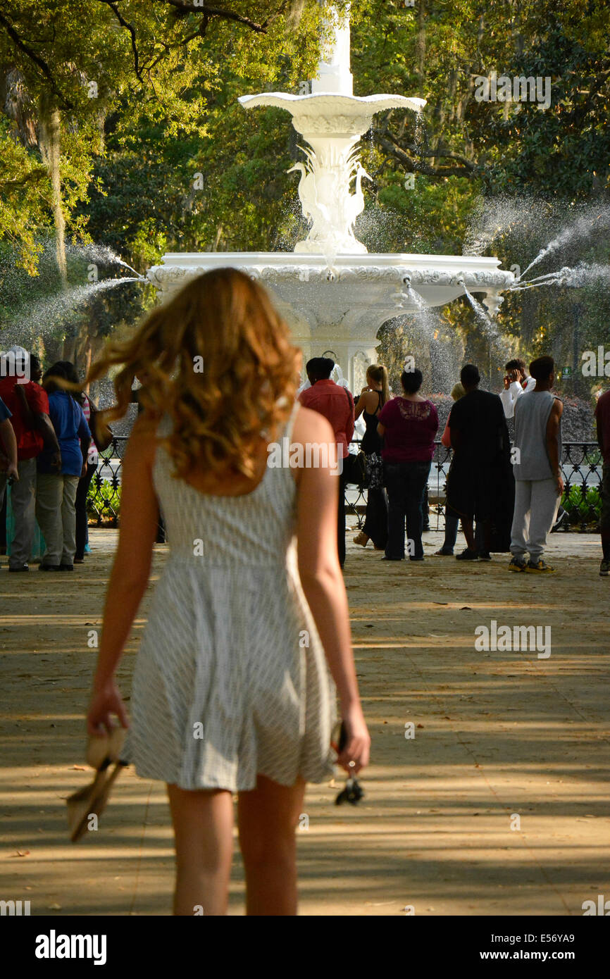 Rear view of a young white female with long hair in a sundress approaching crowd in Forsyth Park near the fountain, Stock Photo
