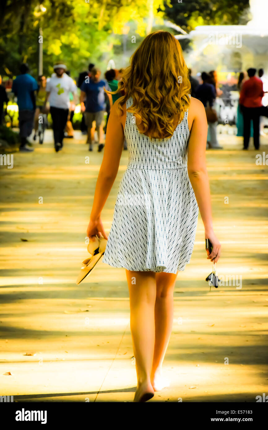 Rear view of a young white female with long hair walking barefoot in a sundress towards the Forsyth Park fountain Stock Photo