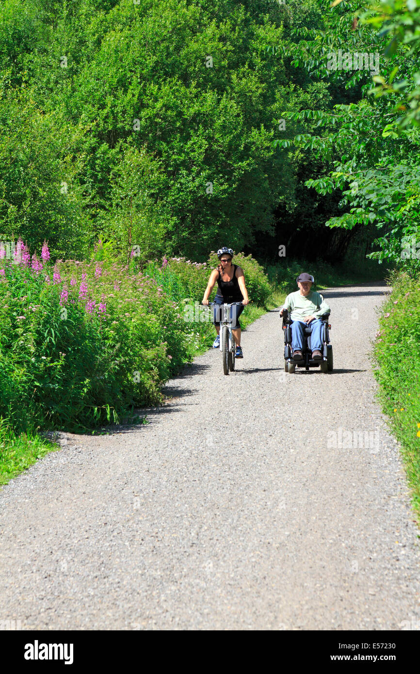 Female cyclist and a male in an electric wheelchair on Monsal Trail in Upperdale, Derbyshire, Peak District National - Stock Image