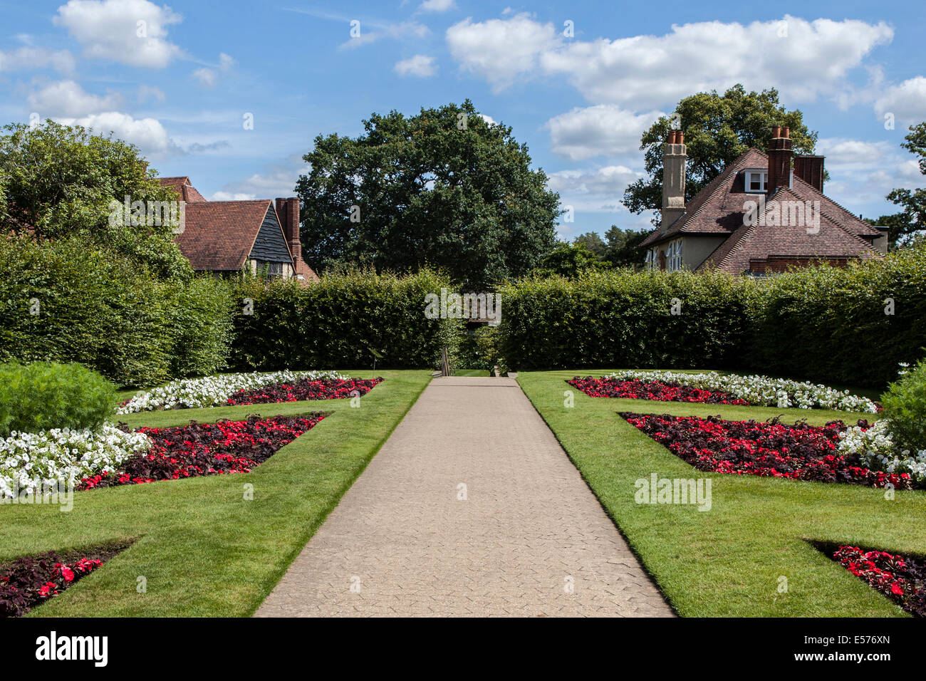 Symmetrical red and white flower beds and bedding plants along a path in Summer at Wisley RHS Gardens, Surrey - Stock Image